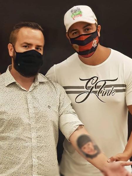 Leniel Borel ao lado do tatuador exibe rosto de Henry no braço - Reprodução/Instagram