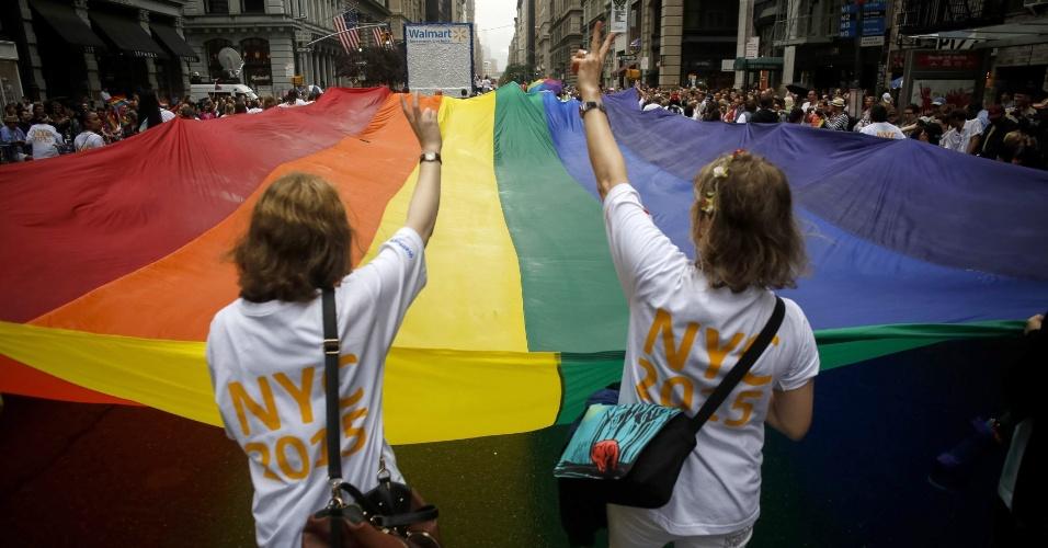 28.jun.2015 - Duas mulheres seguram uma bandeira de arco-íris durante a Parada do Orgulho Gay, ao longo da 5ª Avenida, em Manhattan, na cidade de Nova York (EUA), neste domingo (28). Uma decisão da Suprema Corte dos Estados Unidos legalizou na sexta-feira (26) o casamento entre pessoas do mesmo sexo, ao derrubar vetos estaduais à união homossexual