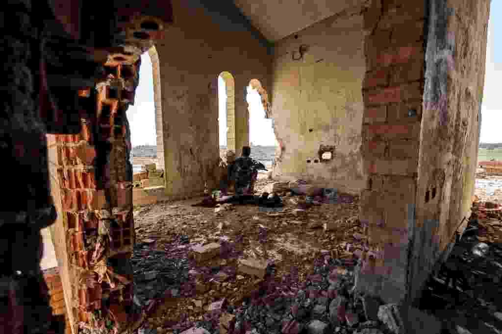 23.jul.2015 - Combatentes da Unidade de Proteção do Povo Curdo (YPG) observam a movimentação do Estado Islâmico em uma construção danificada na cidade de Hasaka, na Síria. A YPG declarou que está próxima de obter o controle do nordeste da cidade, o que seria a maior vitória para região autônoma curda que luta em parceria com os Estados Unidos - Rodi Said/Reuters