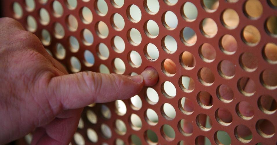 """9.fev.2012 - Um guarda (à esq.) """"cumprimenta"""" preso com o dedo mindinho na unidade de alojamento seguro, onde os prisioneiros são mantidos em isolamento em celas sem janelas"""