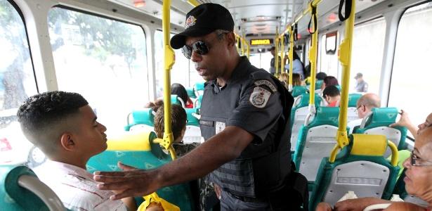 Policial aborda passageiro de ônibus em barreira montada pela PM em Bonsucesso, na zona norte do Rio de Janeiro, neste sábado - Marcos Arcoverde/Estadão Conteúdo