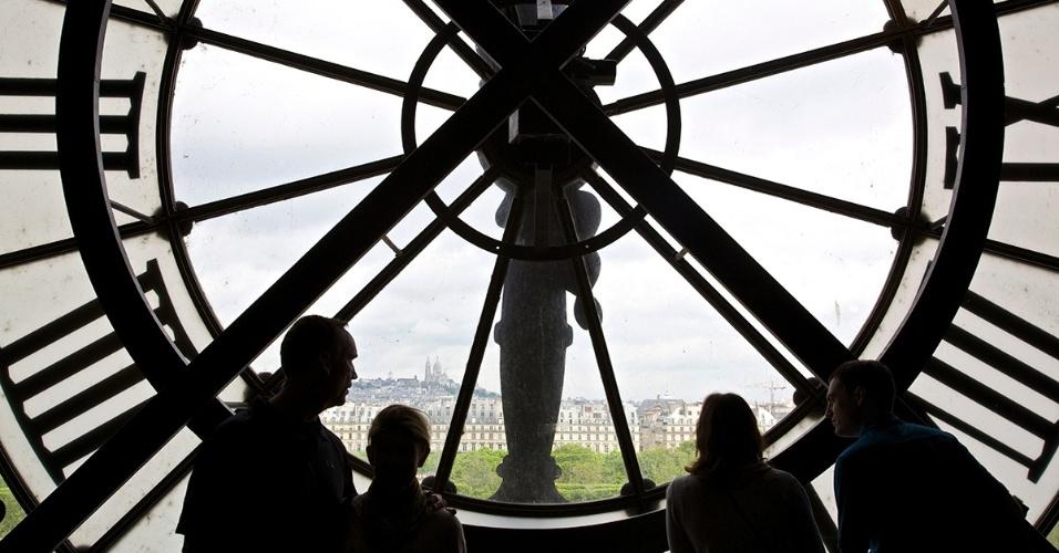 22.dez.2015 - Turistas observam Paris, na França, pelo icônico relógio do Museu de Orsay. O local era uma estação de trem, construído no século 19 num estilo conhecido como Beaux-Arts