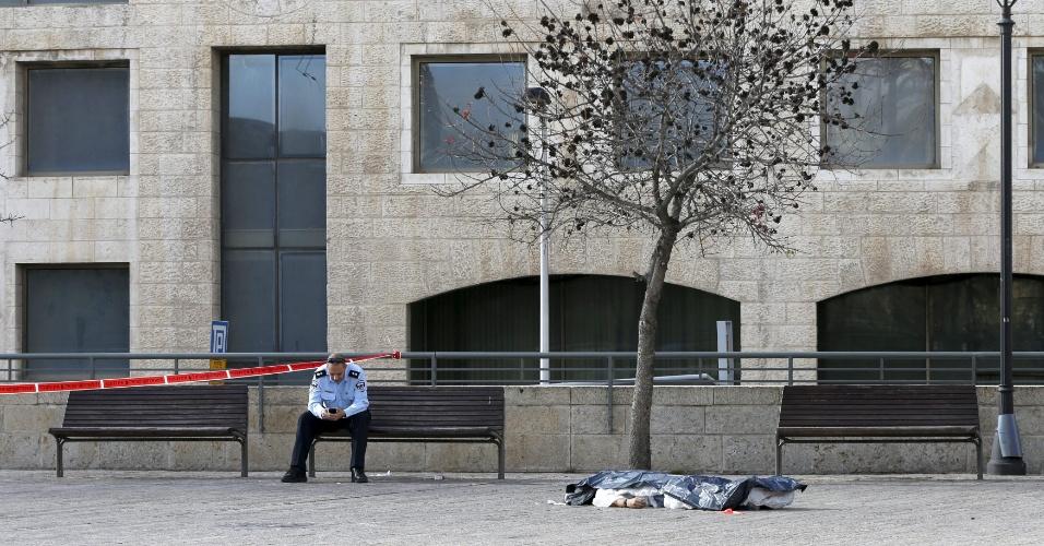 26.dez.2015 - Policial israelense ao lado do corpo de um palestino que foi morto pela polícia em Jerusalém. Segundo o governo do país, o homem foi atingido por tiros depois de tentar esfaquear um agente de segurança. Desde outubro, pelo menos 138 palestinos já morreram em confrontos com as forças de segurança israelenses na onda de violência que atinge a região. Os ataques palestinos, a maioria com arma branca, mas também com armas de fogo, já deixaram 21 israelenses e três estrangeiros mortos