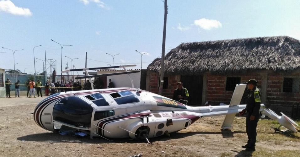 28.dez.2015 - Policiais colombianos protegem helicóptero da Guarda Nacional da Venezuela que caiu na fronteira entre os dois países