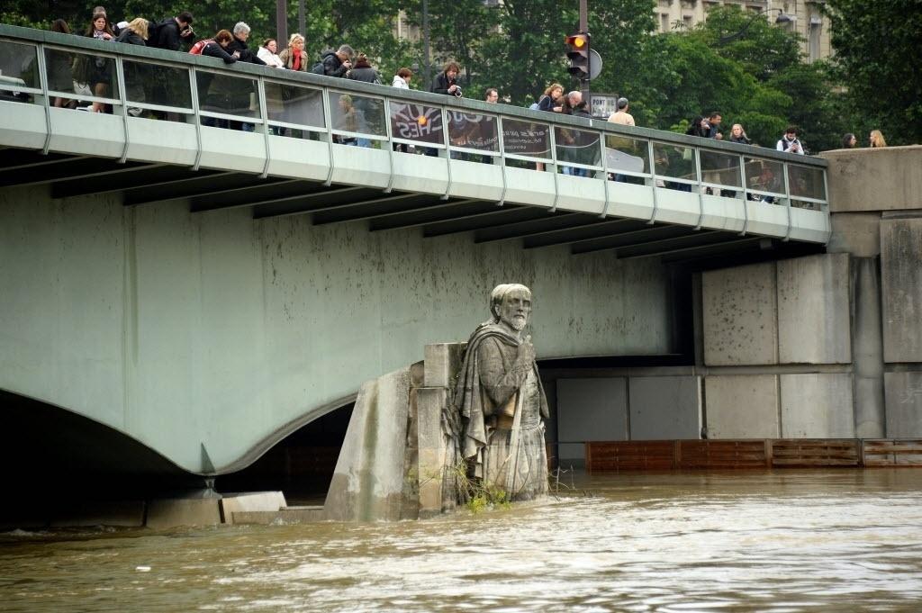 """2.jun.2016 - Uma das estátuas da Ponte de l'Alma, em Paris, fica coberta até a """"cintura"""" por água com a cheia do rio Sena. Chuvas torrenciais caíram nos últimos dias pela Europa e prejudicaram cidades da França e Alemanha"""