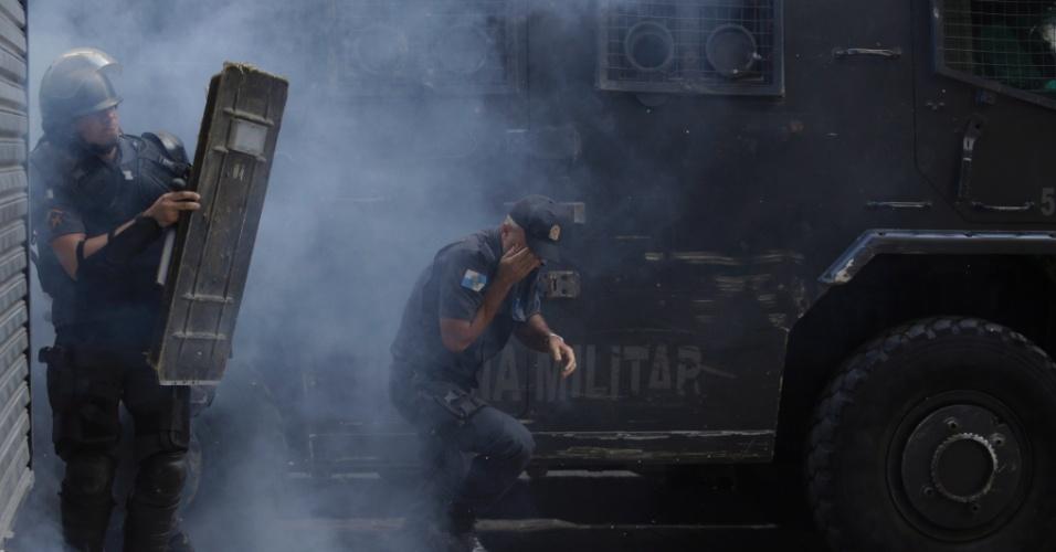 9.fev.2017 - Policial tenta se proteger de fumaça durante confronto com manifestantes no Centro do Rio. Manifestantes mascarados entraram em confronto com policiais militares em frente ao Palácio Tiradentes, sede da Alerj, no Centro do Rio, na tarde desta quinta-feira. A confusão começou quando os manifestantes lançaram fogos e pedras na direção dos policiais, que estavam na frente do palácio. Os agentes revidam com balas de borracha e gás lacrimogêneo