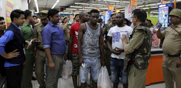 Policiais indianos e curiosos cercam africanos em shopping center em Greater Noida, cidade satélite de Nova Délhi, na Índia