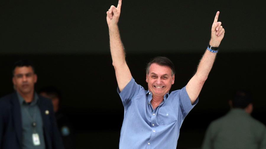 Presidente Jair Bolsonaro acena para apoiadores em frente ao Palácio do Planalto -