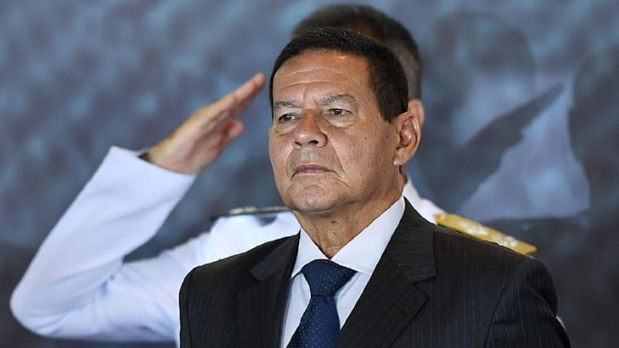 Hamilton Mourão, vice-presidente, à frente de um militar que presta continência - Evaristo Só/AFP