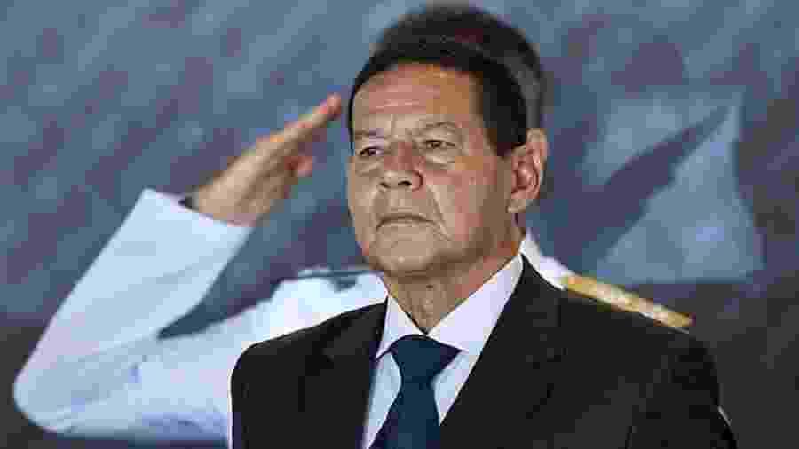 Hamilton Mourão, vice-presidente, à frente de um militar que bate continência - Evaristo Só/AFP