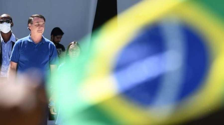 """Bolsonaro observa apoiadores que foram ao seu encontro em Brasília em meio a pandemia de coronavírus; editorial do periódico inglês Lancet afirma que brasileiros deveriam dizer """"E daí"""" para presidente - AFP"""