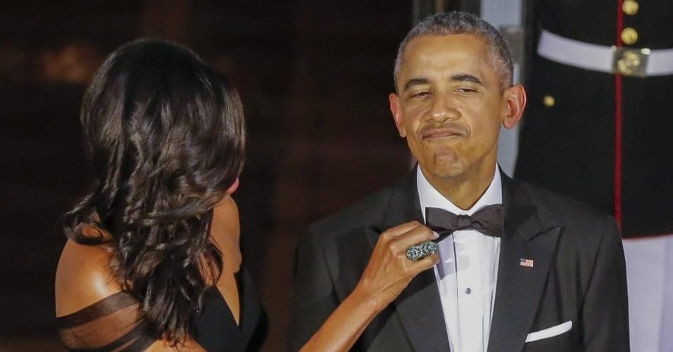 25.set.2015 - A primeira-dama dos EUA, Michelle Obama, ajeita a gravata-borboleta do presidente dos EUA, Barack Obama, enquanto aguardam para cumprimentar o presidente da China, Xi Jinping, e a sua mulher, Peng Liyuan, no Pórtico Norte da Casa Branca, em Washington (EUA), para um jantar em homenagem aos visitantes