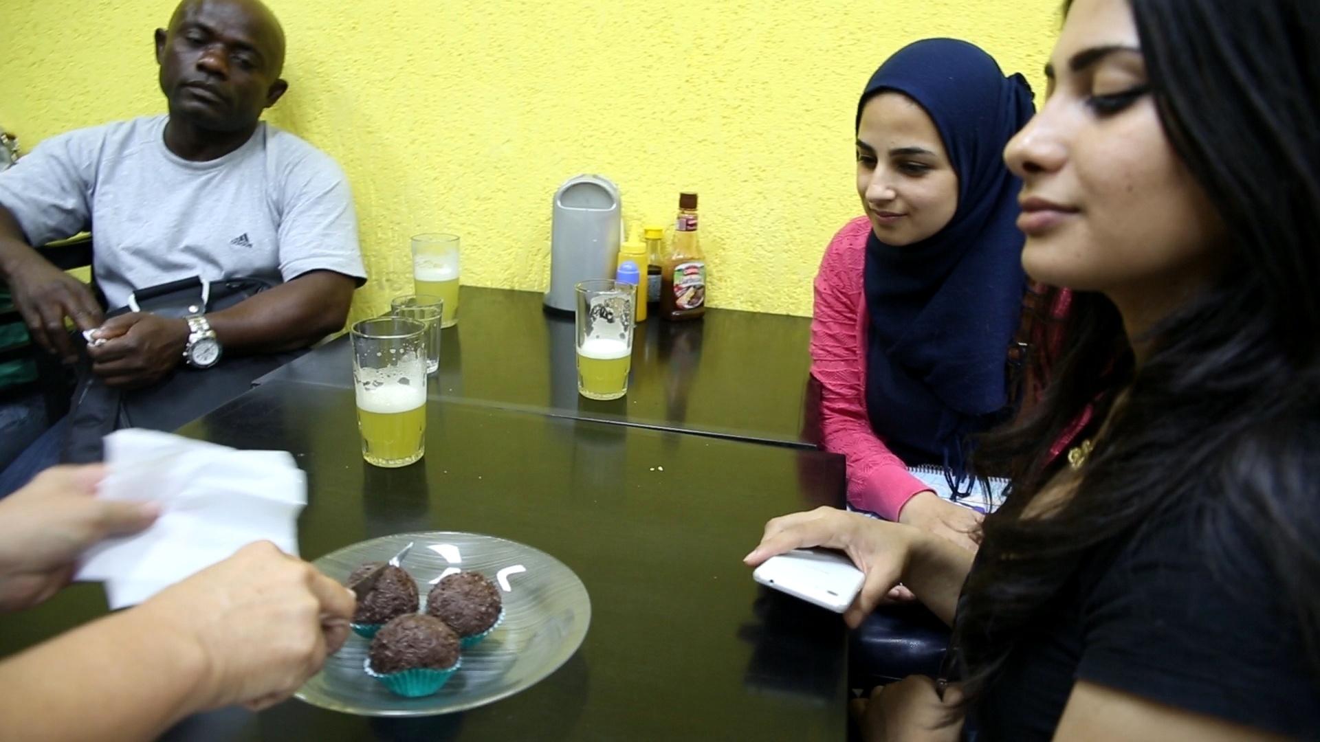 Refugiados alunos do curso de português do Memoref, da Unifesp, comem brigadeiro em bar de Guarulhos, na Grande São Paulo, durante atividade para conhecer a cultura brasileira. Foi a primeira vez em que eles provaram o doce tradicional brasileiro