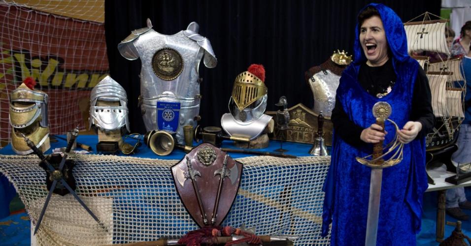 23.jan.2016 - Homens e mulheres podem participar dos combates. Na foto, uma moça fantasiada com trajes históricos acompanha o evento, ao lado de vários equipamentos utilizados nas lutas