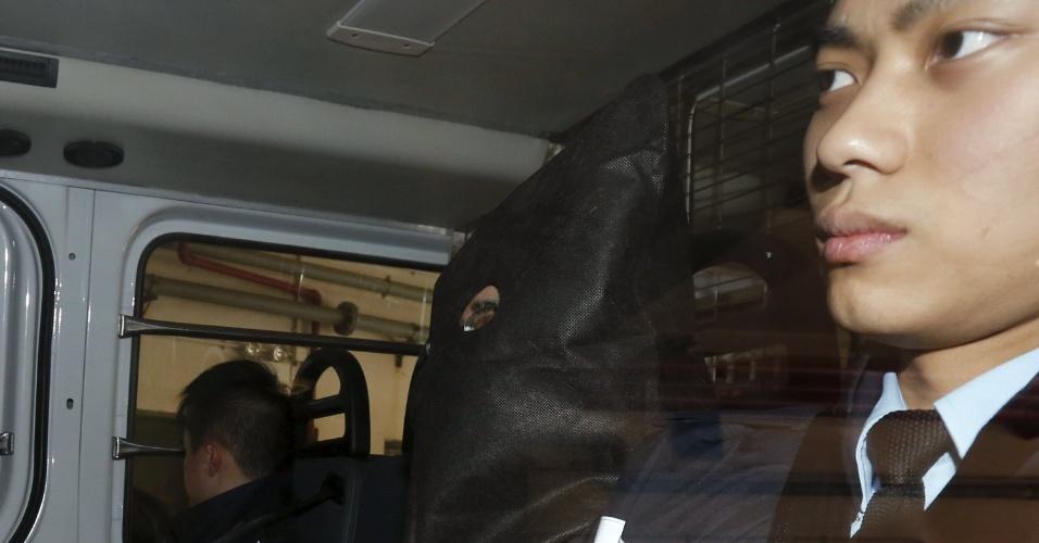 25.jan.2016 - O chinês Deyun Shi (com máscara) chega a um tribunal magistrado em Hong Kong, nesta segunda. A polícia de Hong Kong disse que prendeu o homem procurado pelas autoridades americanas pela suspeita de matar duas pessoas e tentar assassinar uma terceira em Los Angeles