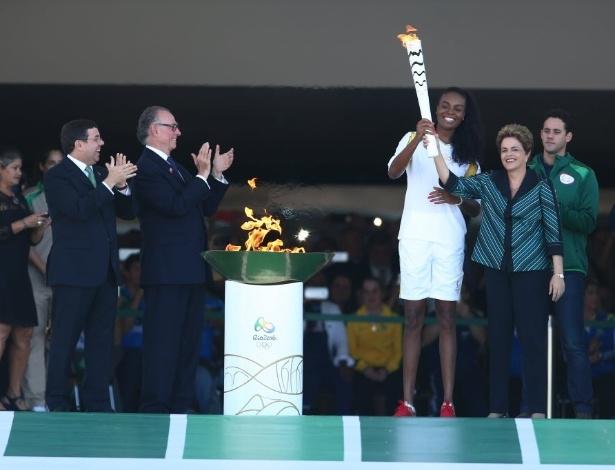 3.mai.2016 - Fabiana Claudino, biicampeã olímpica nas Olimpíadas de Pequim, segura a tocha olímpica ao lado da presidente Dilma Rousseff. O fogo sagrado foi aceso em 21 de abril, em cerimônia realizada na cidade grega de Olímpia. O revezamento da tocha no Brasil vai durar três meses e se encerrará em 5 de agosto, no Rio de Janeiro, na abertura oficial dos Jogos Olímpicos de 2016