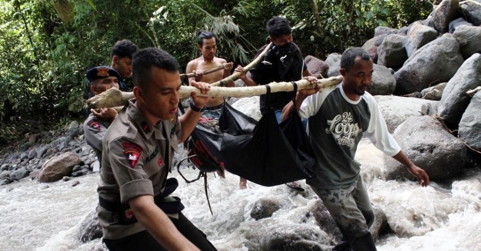 16.mai.2016 - Policiais e voluntários carregavam corpo de vítima de inundação em Sumatra, Indonésia. Pelo menos dezessete pessoas morreram. As vítimas eram estudantes universitários que passavam o fim de semana acampados na região e foram surpreendidos por uma enchente durante visita a uma cachoeira