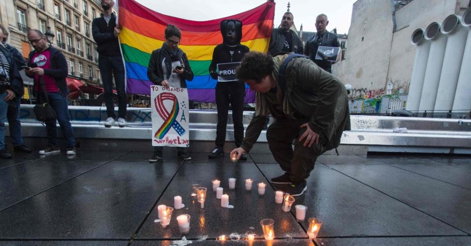 12.jun.2016 - Manifestantes seguram a bandeira do arco-íris, símbolo do movimento LGBT, durante vigília próxima ao centro de artes Beaubourg, em Paris (França), em memória às vítimas do massacre na boate gay Pulse, em Orlando, na Floria (EUA). O norte-americano Omar Mateen, 29, abriu fogo dentro do local mantando 50 pessoas e ferindo 53