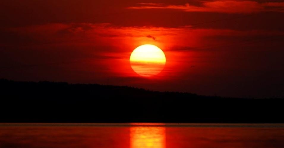25.jun.2016 - Pôr do sol deixa o céu avermelhado em um lago perto da aldeia de Novoselki, na Bielorrússia