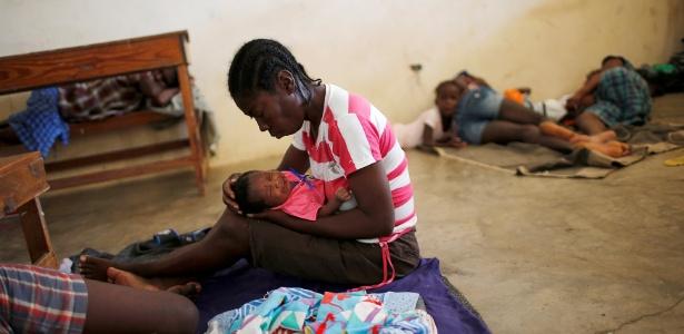 8.out.2016 - Mulher segura seu bebê em abrigo montado em uma escola de Jeremie, no Haiti, após a passagem do furacão Matthew