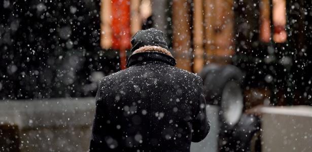 Homem olha o telefone em meio à neve em Wall Street, Nova York