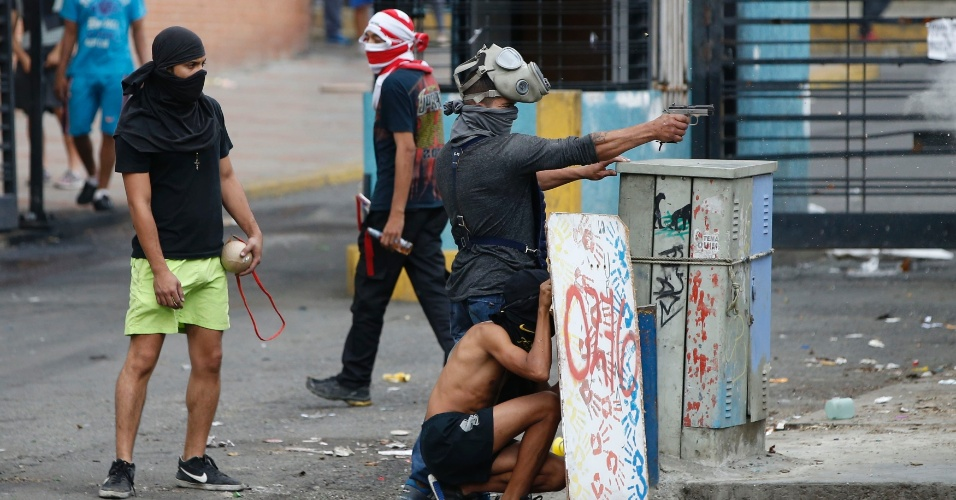 30.jul.2017 - Manifestante aponta pistola durante confrontos com as forças de segurança