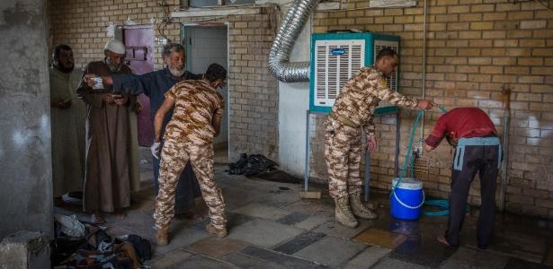 Homens suspeitos de serem ex-combatentes do EI são vistoriados em centro de segurança em Kirkuk, no Iraque