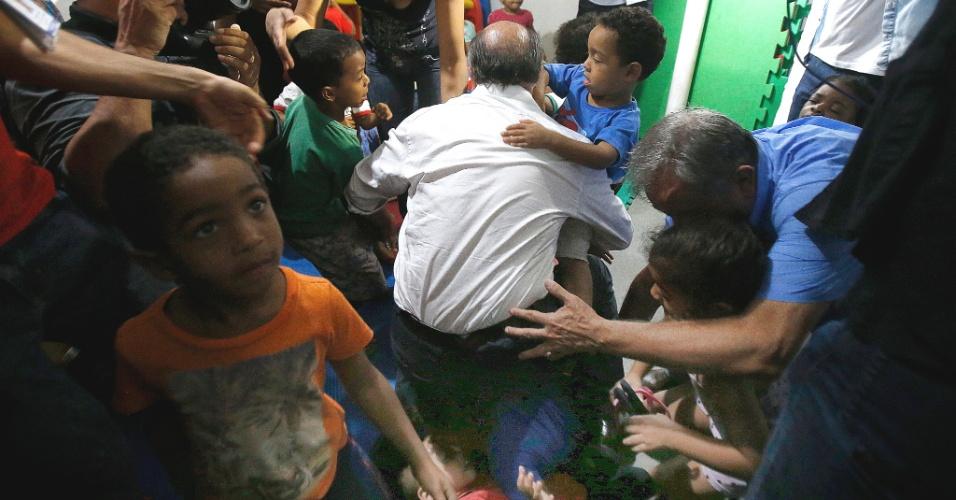 17.set.2018 - O candidato do PSDB à Presidência da República, Geraldo Alckmin, tropeçou e caiu com uma criança no colo durante visita a uma creche comunitária na Cidade Estrutural, uma das regiões administrativas mais carentes do Distrito Federal