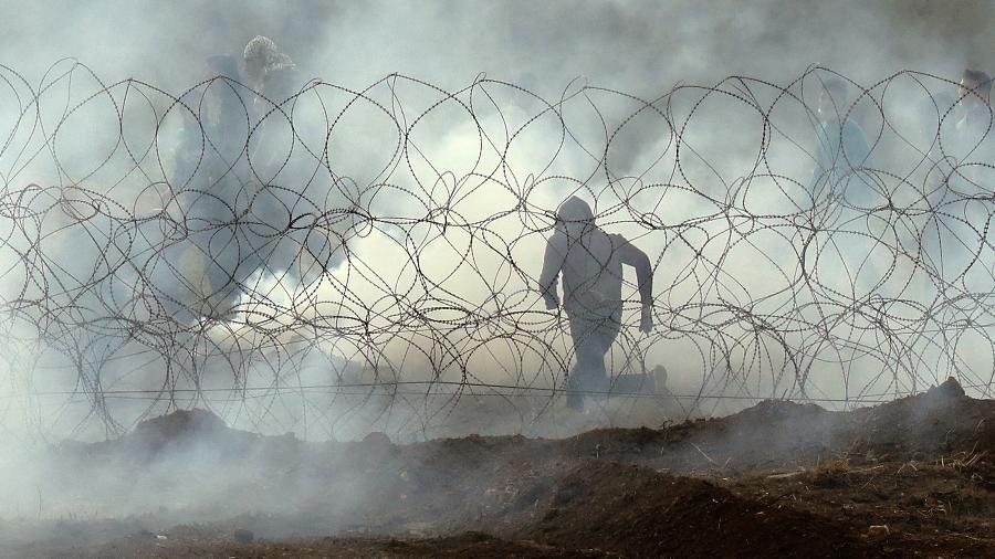"""Kibutz do sul de Israel de Nahal Oz, na fronteira da Faixa de Gaza, mostra um manifestante palestino fugindo da cerca da fronteira, como os palestinos demonstram para marcar o primeiro aniversário da """"Marcha de Retorno"""" protestos. - JACK GUEZ/AFP"""