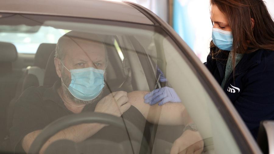 6.jan.2021 - Homem é vacinado contra o novo coronavírus em centro de vacinação drive-through em Haifa, Israel - Ammar Awad/Reuters