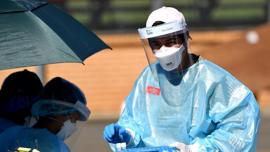 Trabalhadores de saúde coletam amostras em uma unidade de testes de covid-19 no subúrbio de Smithfield, em Sydney - Saeed Khan/AFP