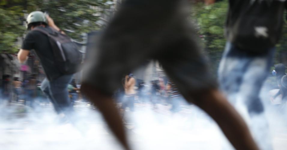 8.jan.2015 - Jovens correm após policiais laçarem bombas de gás durante confusão em ato contra o aumento do valor da tarifa do transporte público de São Paulo, no centro de São Paulo. Neste sábado (9), tarifa passa de R$ 3,50 para R$ 3,80