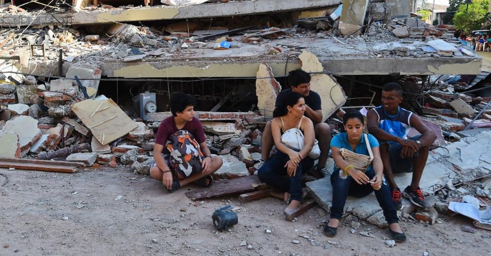 17.abr.2016 - Pessoas descansam diante de prédios destruídos em Manta, no Equador