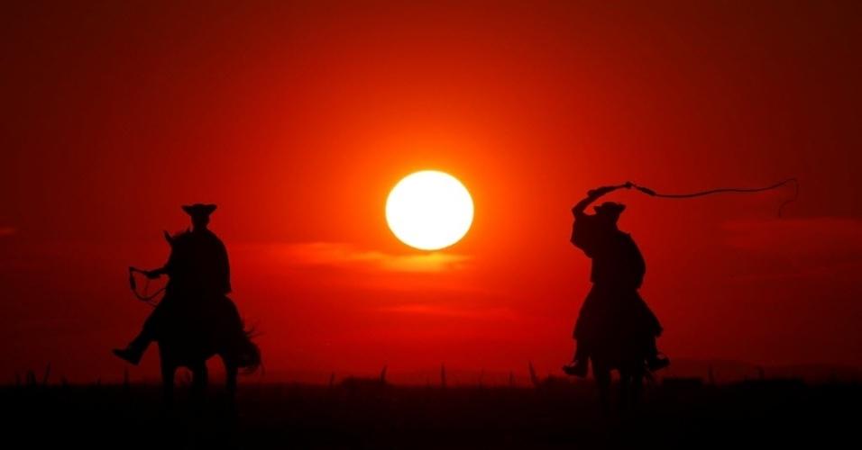 7.jul.2016 - Cavaleiros tradicionais húngaros treinam durante o pôr do sol na Grande Planície húngara, em Hortobagy