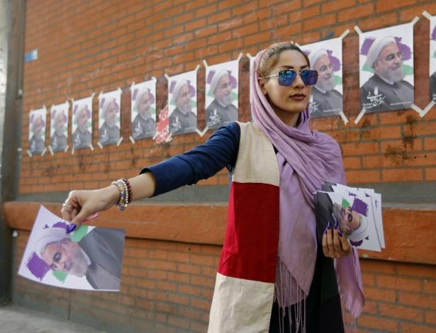 Simpatizante distribui imagem do presidente e candidato a reeleição Hassan Rouhani, nas ruas de Teerã