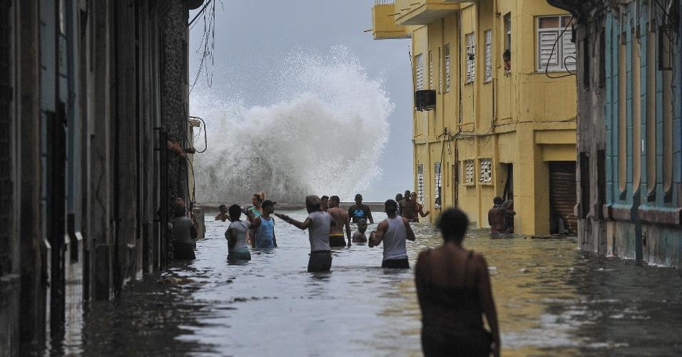 10.set.2017 - Cubanos andam por rua debaixo d'água em Havana após a passagem do furacão Irma