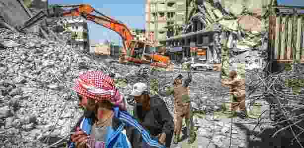 Homens coletam sucata de metal dos escombros da Praça Paradise Square, que costumava ser um próspero centro comercial, em Raqqa, na Síria - Ivor Prickett/The New York Times - Ivor Prickett/The New York Times