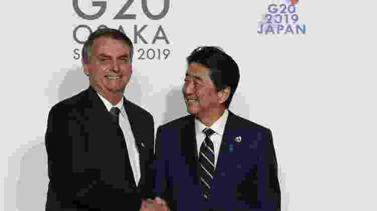 O presidente Jair Bolsonaro com o primeiro-ministro do Japão, Shinzo Abe, durante reunião do G20 em Osaka, em junho de 2019 - KIM KYUNG-HOON / POOL / AFP