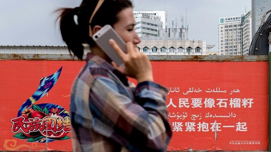 Mulher usa celular na região autônoma de Xinjiang, no noroeste chinês - Zhang Peng/LightRocket/Getty Images
