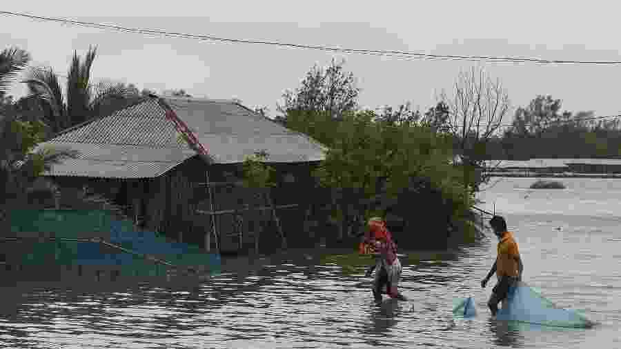 Moradores de Shyamnagar, na Índia são vistos em meio ao estragado causado pelo ciclone Amphan - Munir Uz zaman / AFP