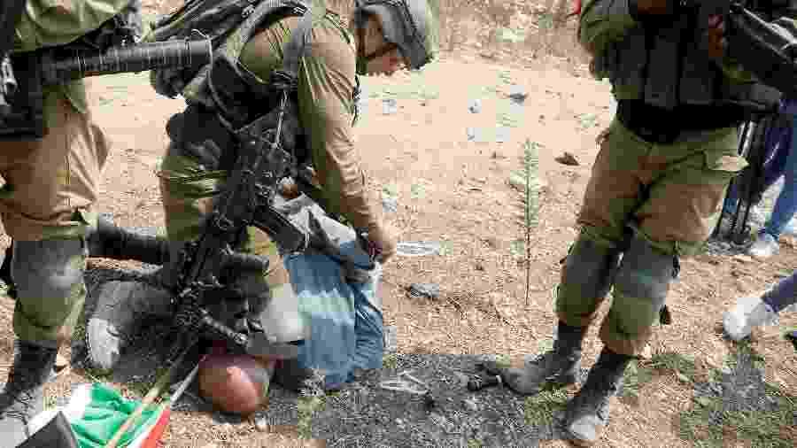 Soldado israelense ajoelhado no pescoço de um militante palestino - RANEEN SAWAFTA/REUTERS