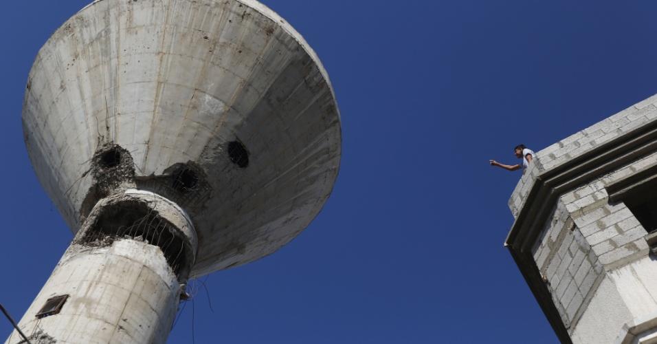 19.set.2015 - Garoto palestino aponta para torre de água alvo de um bombardeio aéreo israelense na cidade de Beit Hanun. na Faixa de Gaza, neste sábado (19). Israel bombardeou Gaza depois que dois foguetes foram disparados contra o sul de Israel por militantes do Hamas, sem causar vítimas