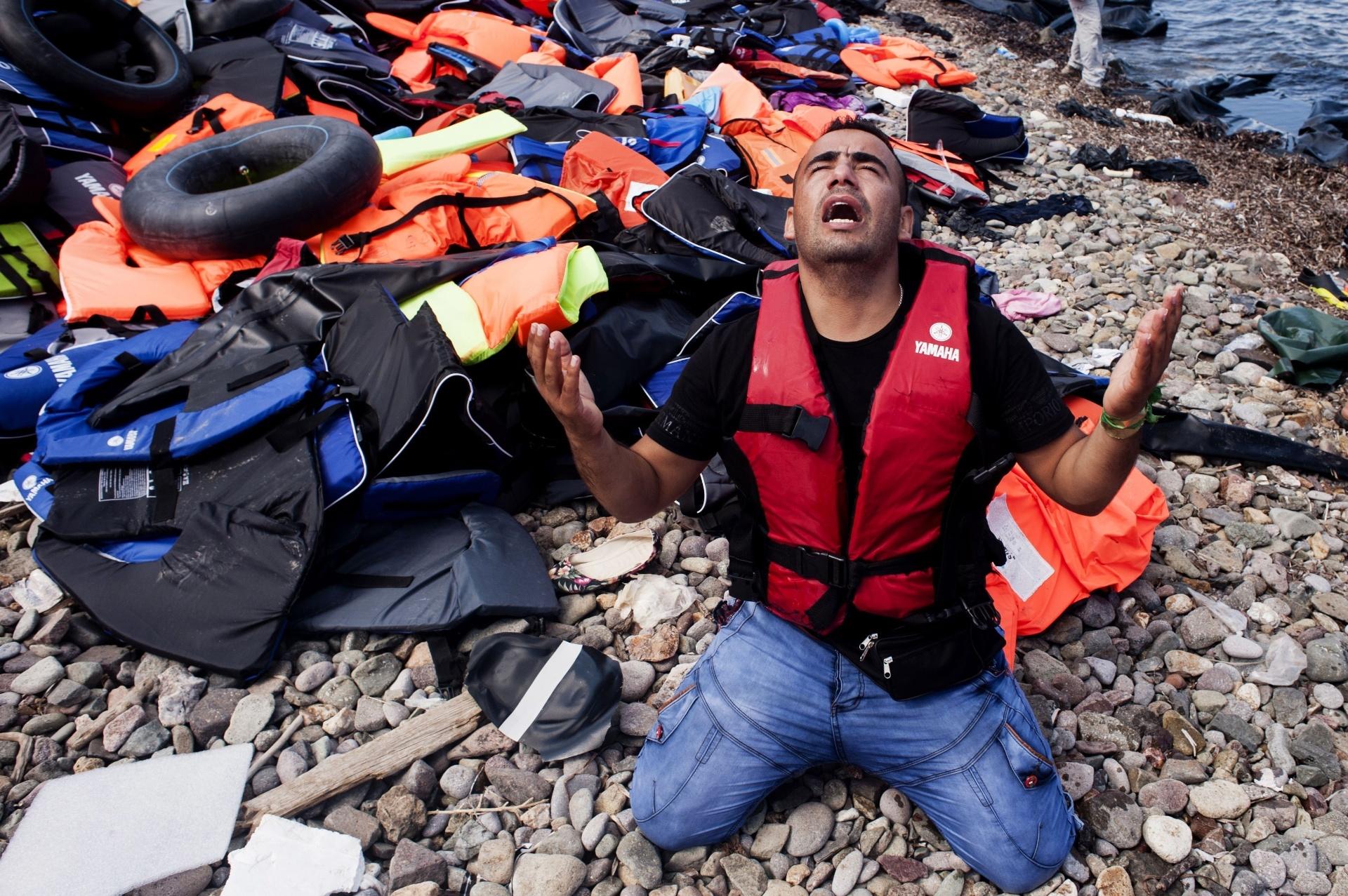 25.set.2015 - Imigrante reza após chegar em bote inflável que cruzou o mar Egeu até a ilha de Lesbo, na Grécia. Nos últimos dias, a chegada de barcaças procedentes da Turquia se multiplicou. Um total de 3.938 refugiados seguiram nesta sexta-feira para o porto ateniense do Pireo
