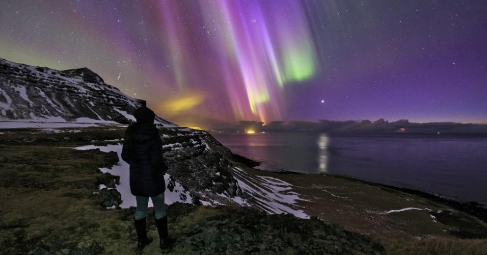 O céu é o limite. Uma mulher na Islândia observa a aurora boreal sobre o Atlântico