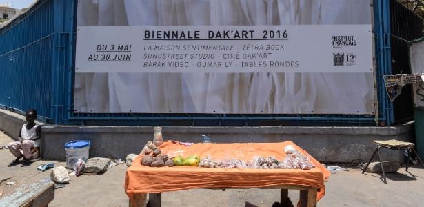Barraca de frutas é vista diante de cartaz da Bienal de Dacar, em Dacar, no Senegal