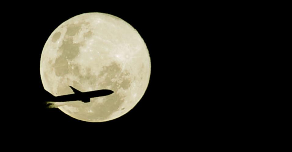 21.mai.2016 - Avião passa pela primeira lua cheia do mês de maio, vista do bairro da Bela Vista, região central de São Paulo