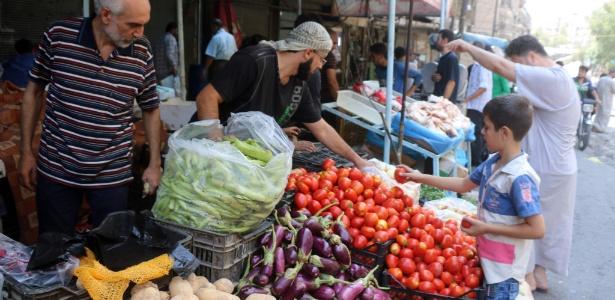Comerciante vende legumes em mercado em Aleppo, Síria