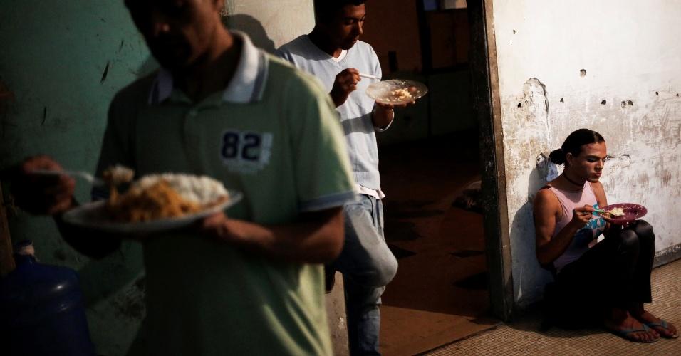 10.nov.2016 - Sentada no chão, a travesti Patrícia (à direita) come ao lado de outros moradores de prédio ocupado no Centro de São Paulo