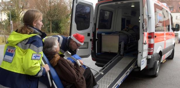 Paramédicos ajudam a retirar idosa de sua casa em Augsburg - Stefan Puchner/AFP