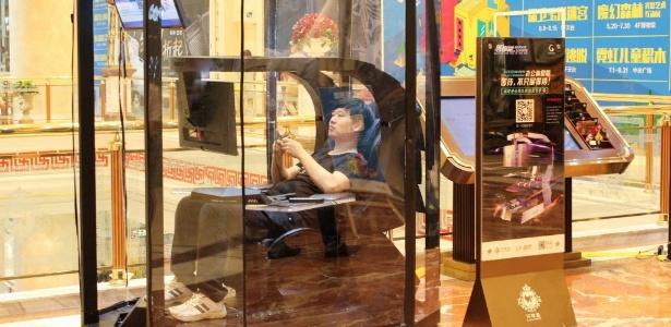 Chinês joga videogame enquanto espera companheira fazer compras - AFP Photo